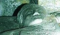 Il primo piano di una statua funeraria conservata nella chiesa e le campane originali dell'800 che si mantengono per miracolo a travi di legno divorate dall'umidità