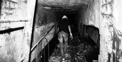lo speleologo Luca Cuttitta di fronte a un immenso accumulo di catrame.