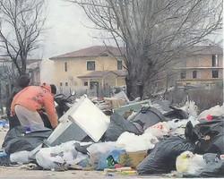 Alcuni ragazzi di Casal di Principe cercano tra i rifiuti che occupano un viale di quasi due chilometri